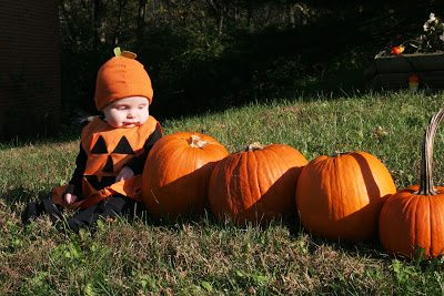 Baby in a Halloween costume in a pumpkin patch