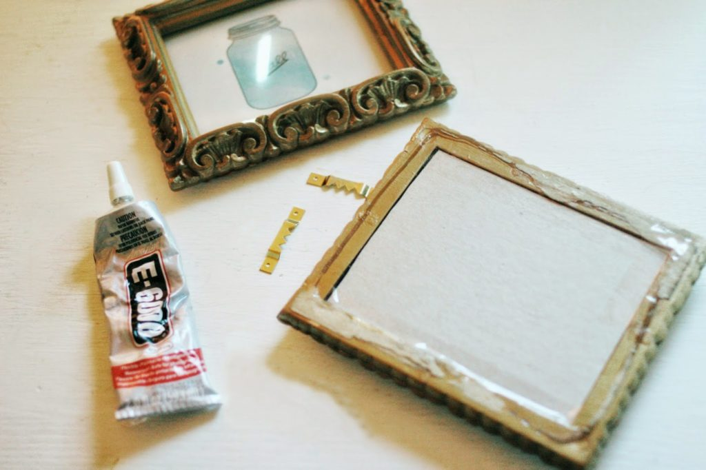 picture frames, glue, and picture hangers being used to attach a hanger to a plastic frame