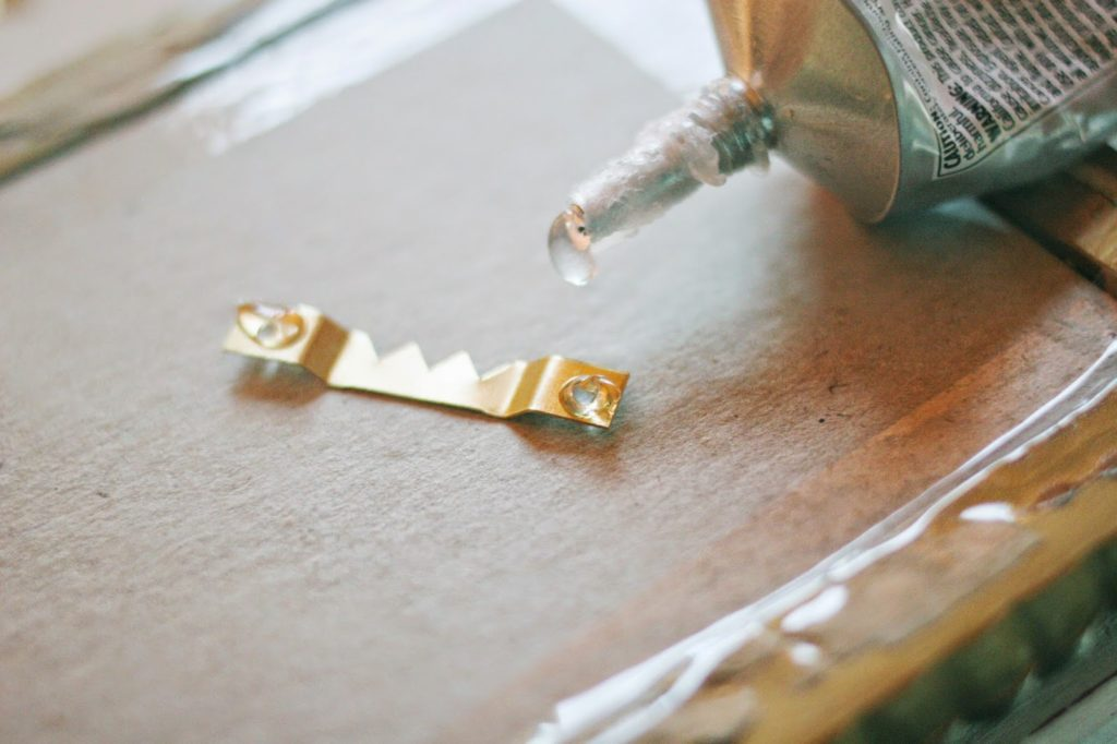 adding glue to a picture hanger