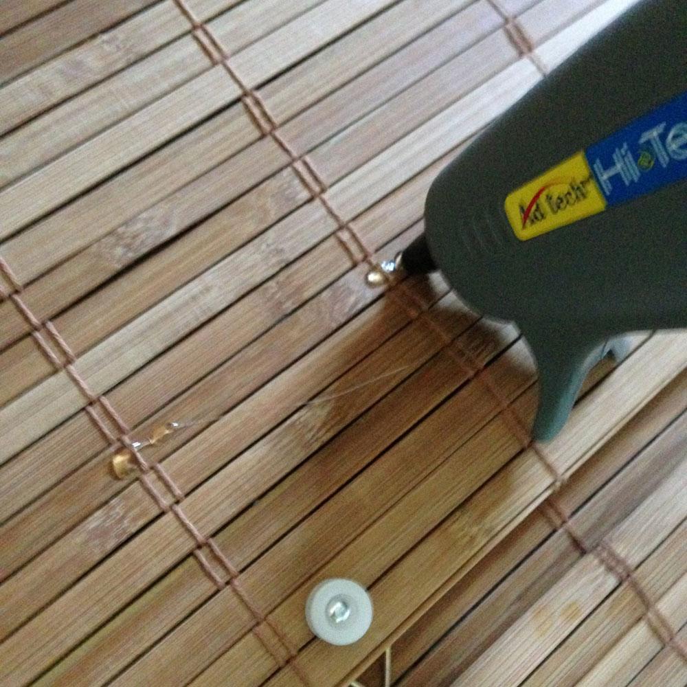 glue gun putting glue on diy bamboo blinds