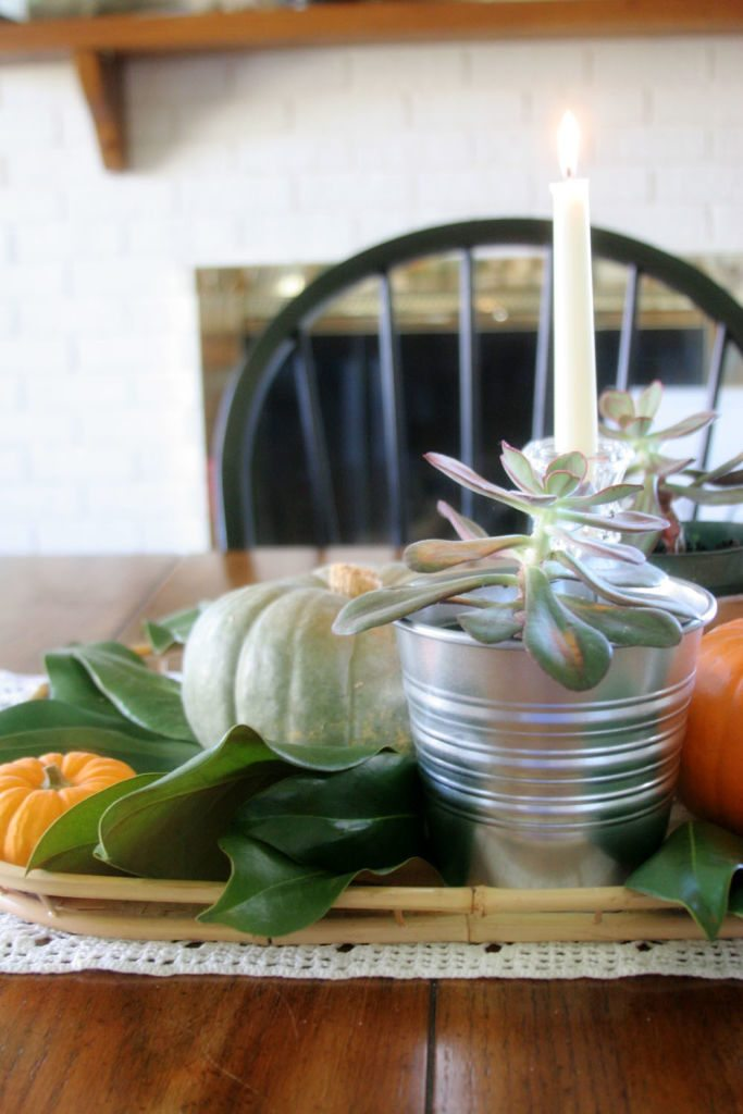 A simple fall centerpiece with pumpkins, magnolia leaves and succulents. #Thanksgiving #Tablescape