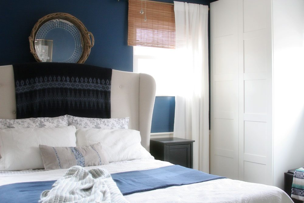 master bedroom, navy walls, upholstered headboard, wardrobes
