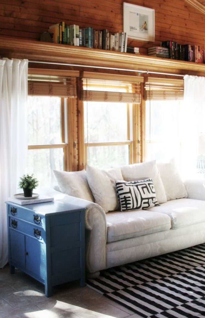 Sunroom makeover progress with wood paneling, white curtains, white furniture, black and green details. Light & Bright Eclectic Home Tour by @CraftivityD