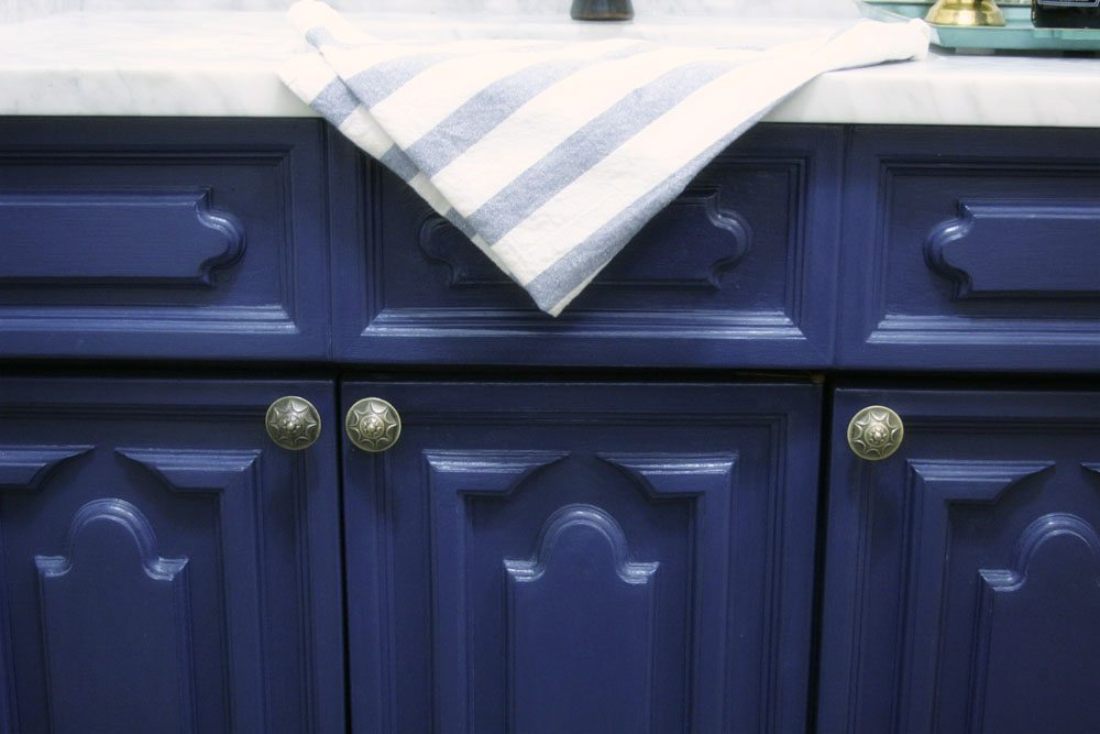 Navy blue vanity with brass knobs used for a bathroom vanity makeover.