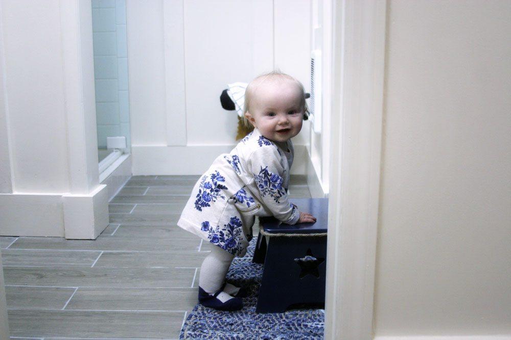 Little girl holding onto a bathroom stool.