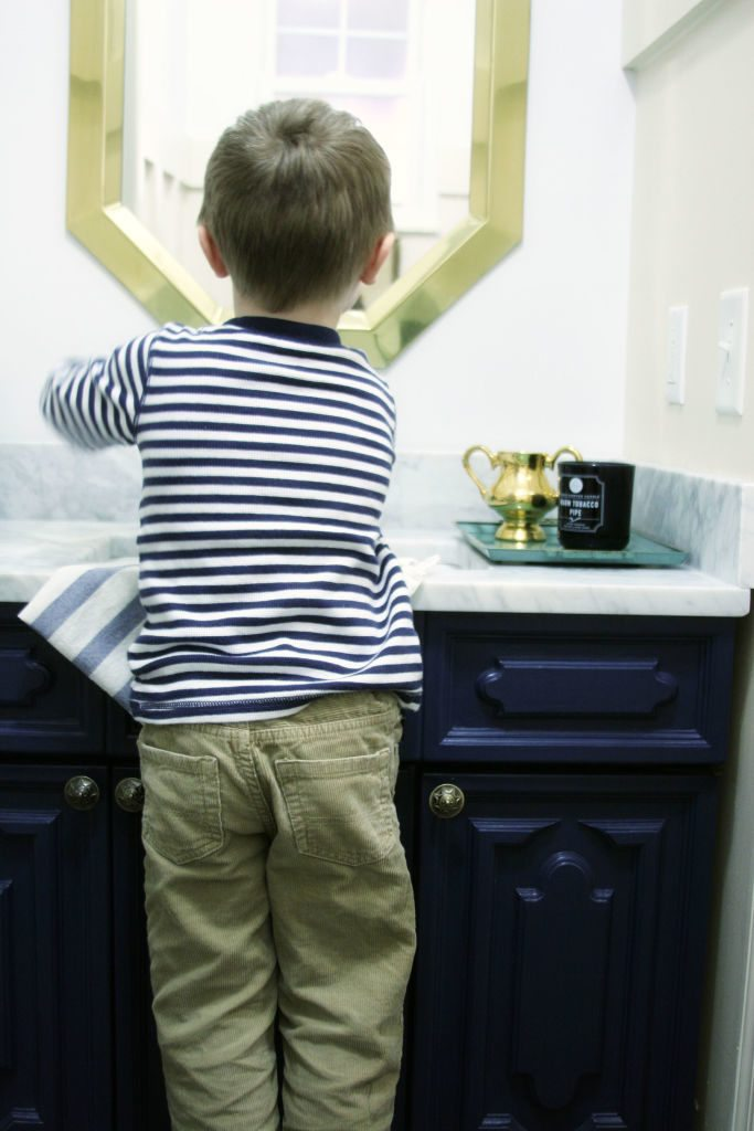 Child washing his hands at a sink with marble counter tops and navy blue cabinets.