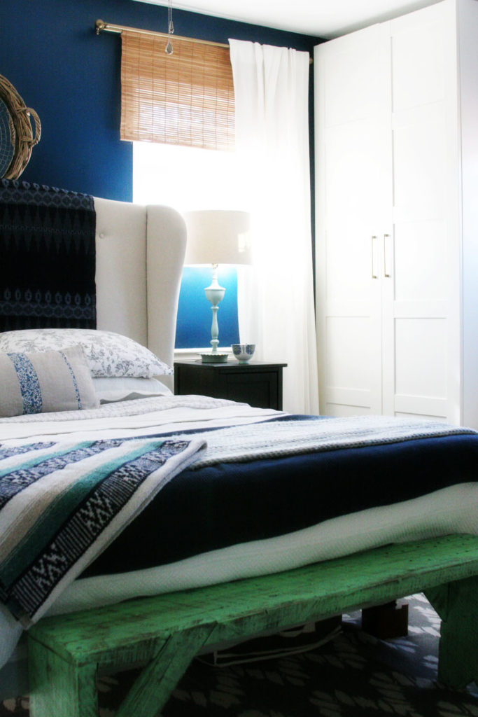 Master Bedroom Makeover // grey rug, navy walls, white curtains, white bedding, upholstered headboard, wood floors, small night stand, gold lamp, bamboo shades // by @CraftivityD