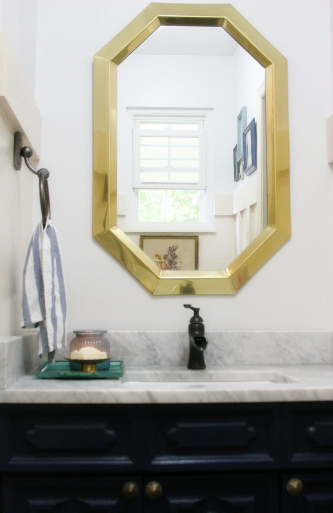 Navy and white bathroom renovation with vintage art, marble, board and batten. Ideas for a small bathroom or guest bath makeover. Light & Bright Eclectic Home Tour by @CraftivityD
