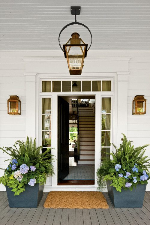 Home with white siding, a black front door idea, and blue planters