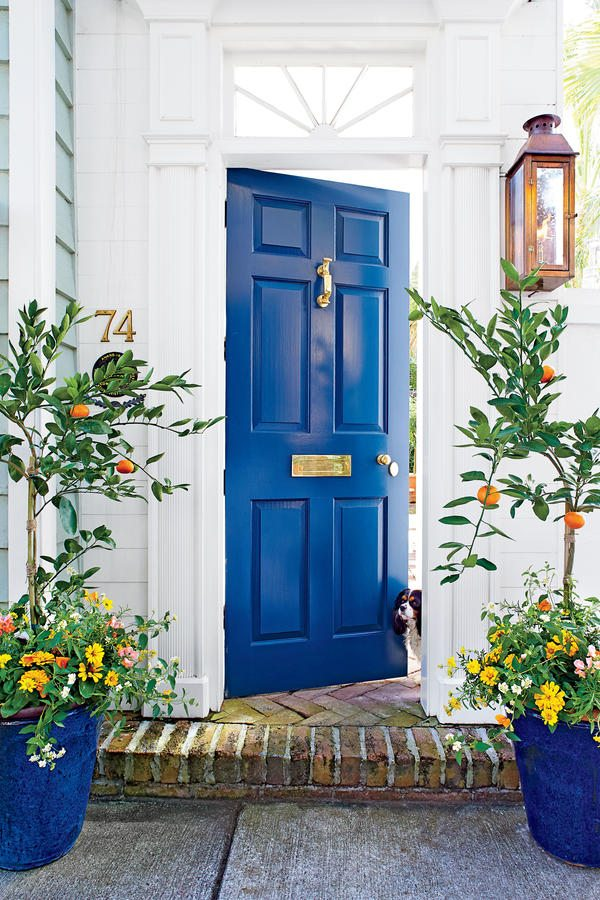 White and blue-green exterior with cobalt blue door and planters