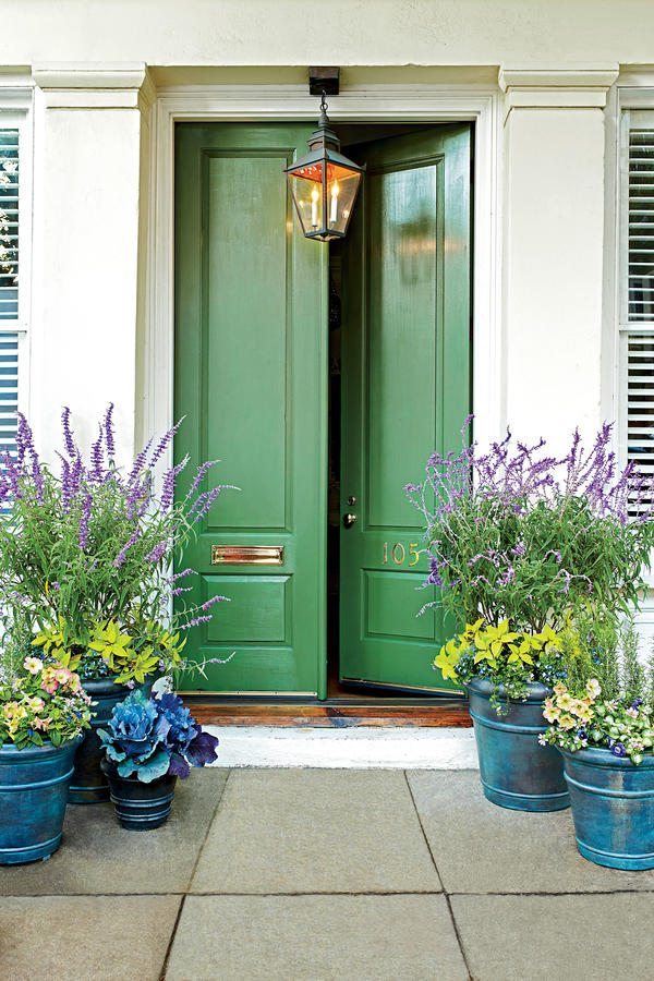 Home with light exterior, a green door idea, and blue planters