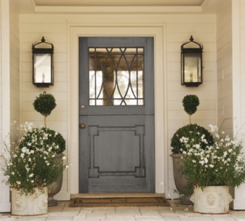 A cream home exterior with a grey door and concrete planners for a front door idea