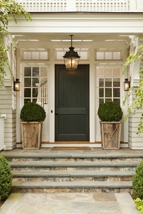 White home with wooden planters and a charcoal front door idea