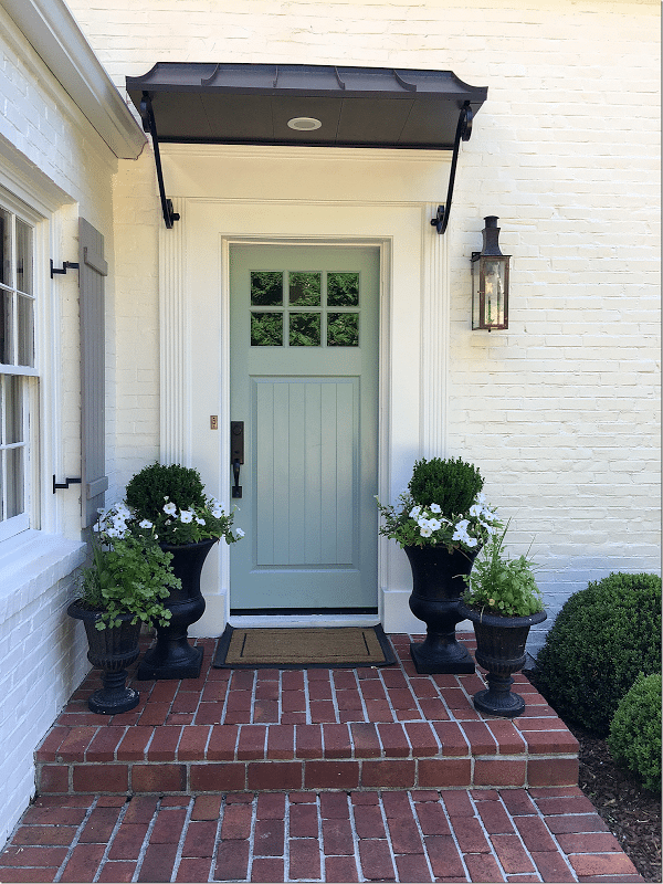 Home with white painted brick and a grey-blue door idea