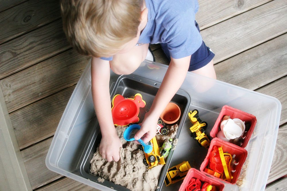 Boy playing with a DIY portable sandbox