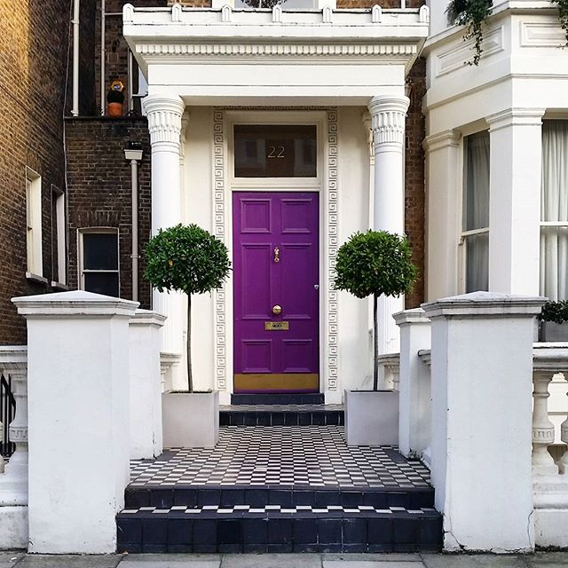 White and brick home exterior with a deep purple front door idea