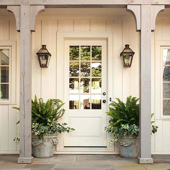 A white home with a white front door idea and concrete planters