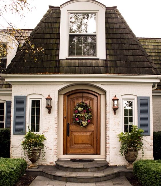 Home with white painted brick and a wooden door idea