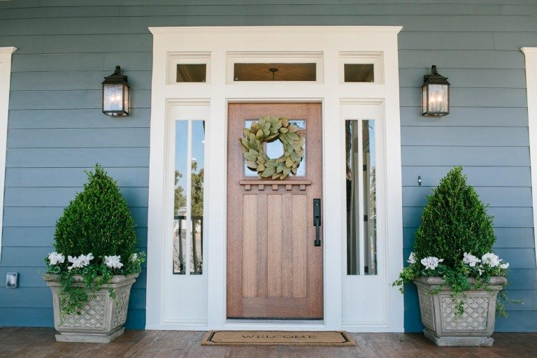 Home with blue-gray siding and a wooden door idea.
