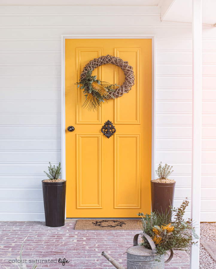 Home with white siding and deep yellow door idea
