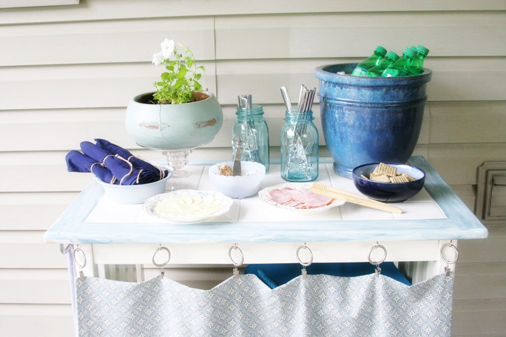 DIY outdoor serving bar with food, drinks, and utensils.