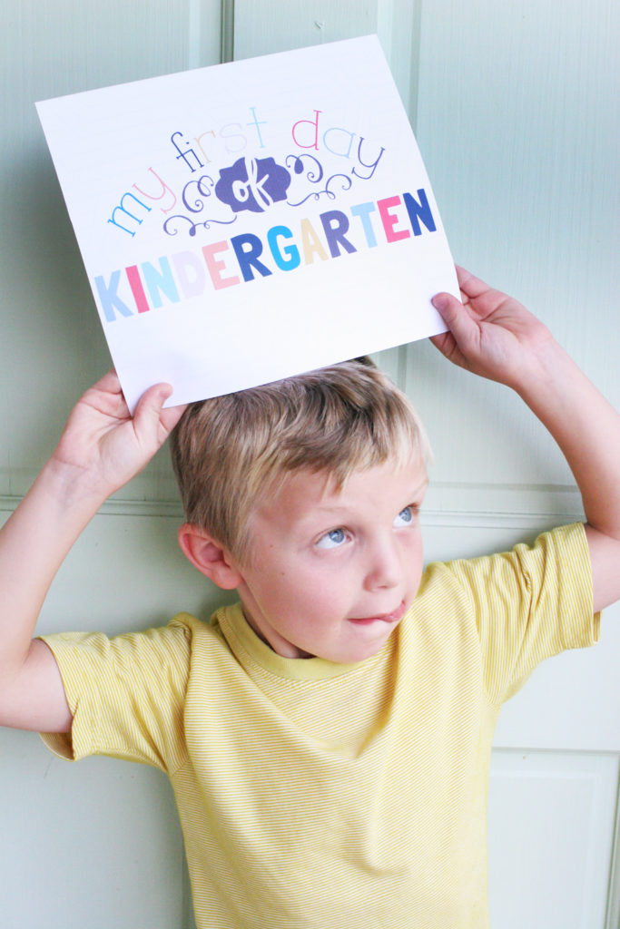 "Boy holding a sign that says ""my first day of kindergarten"""