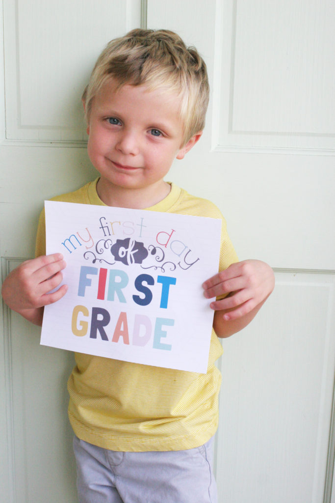 "Boy with a printable sign reading ""my first day of first grade"""