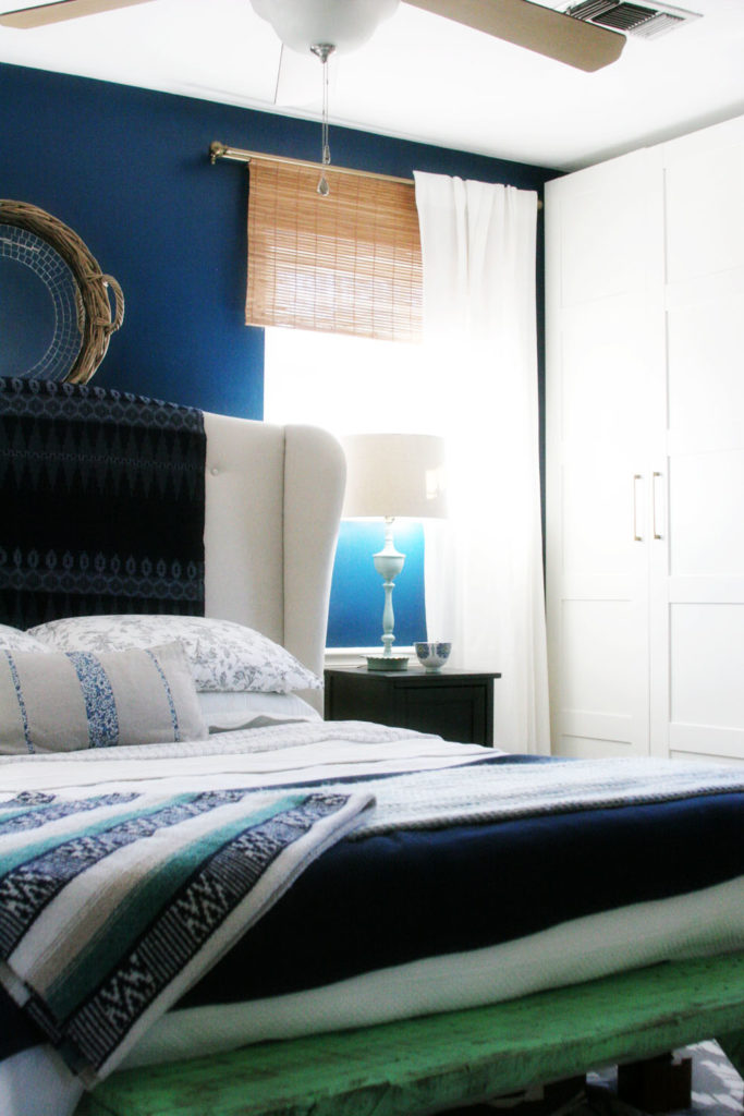 A navy master bedroom, featuring white bedding, bamboo blinds, an upholstered headboard and plenty of storage with large wardrobes and a smart floor plan.