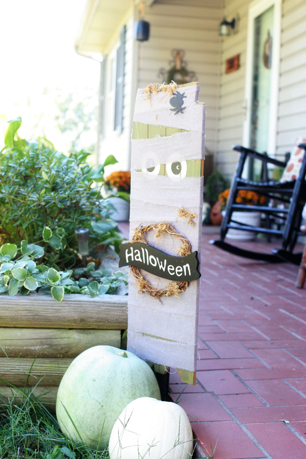 Cute pumpkin display and wooden mummy sign used as DIY outdoor Halloween decorations