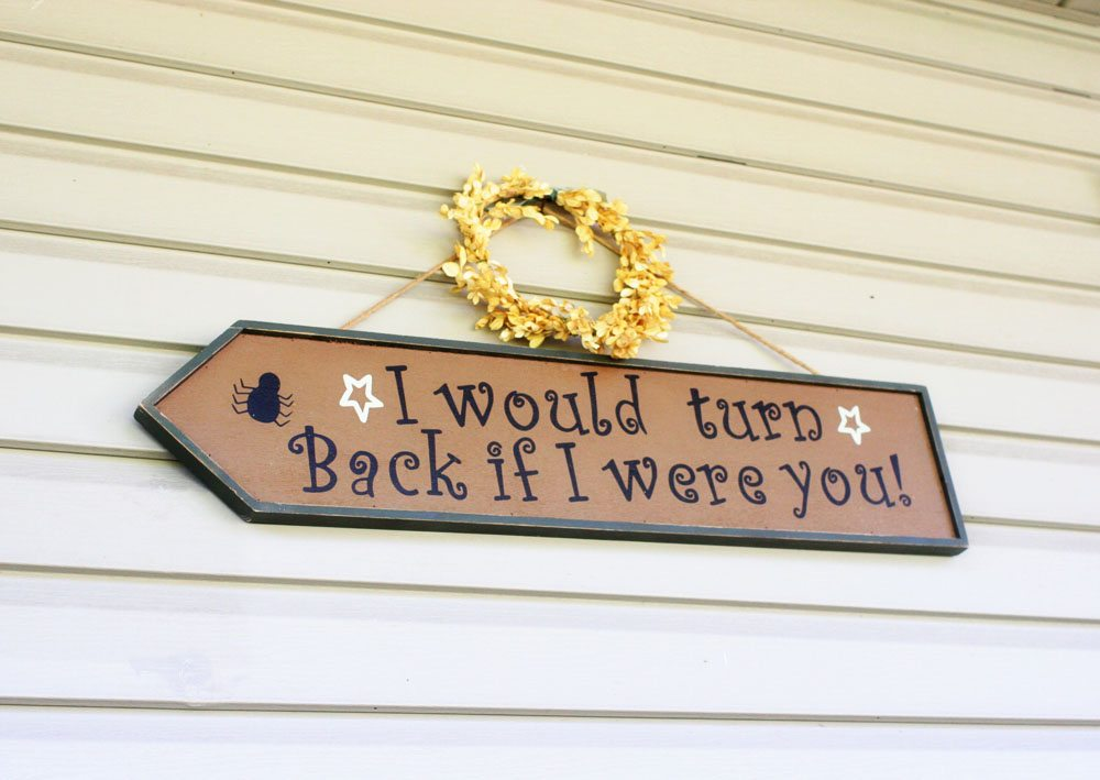 "An outdoor Halloween sign reading ""I would turn back if I were you!"""