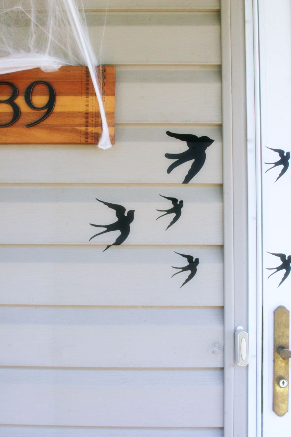 Flying bird adhesives on the side of a house used for DIY outdoor Halloween decorations