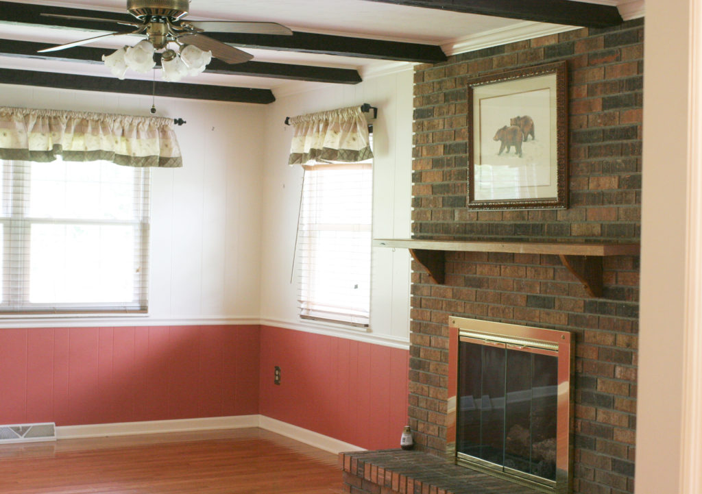 dining room BEFORE with dark brick fireplace and coral walls