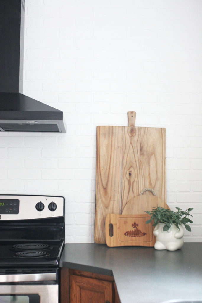 blank range hood, brick backsplash, bread boards