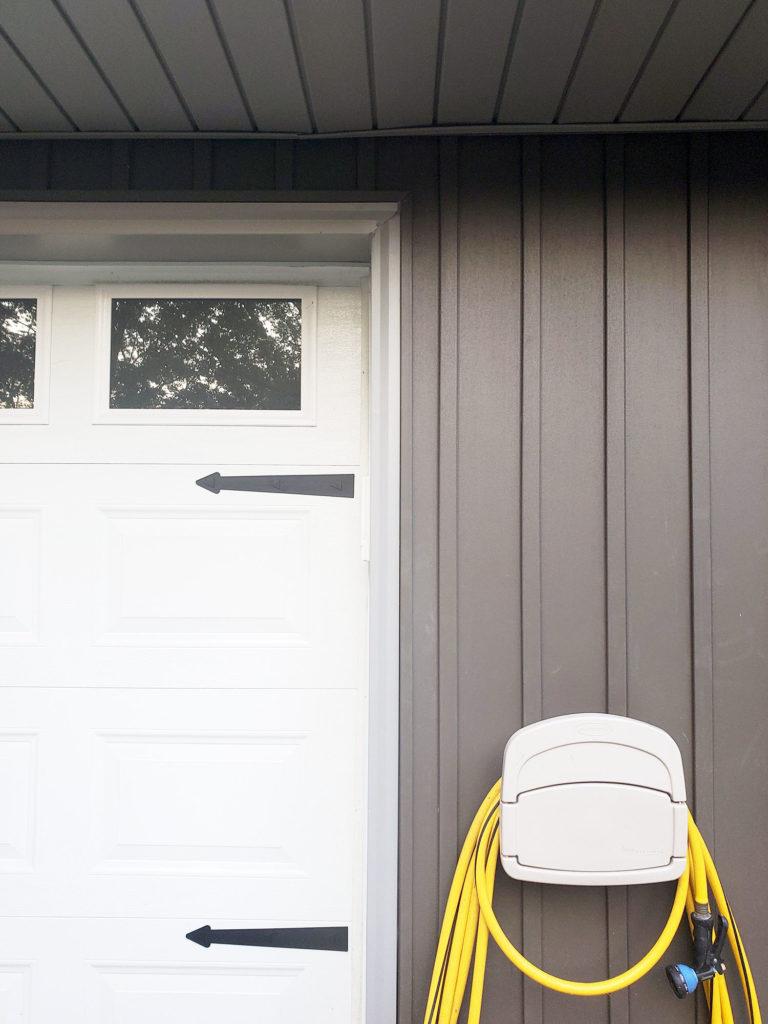 Dark Gray Board and Batten Siding (Vertical Siding), White Garage Door, and Water Hose Storage