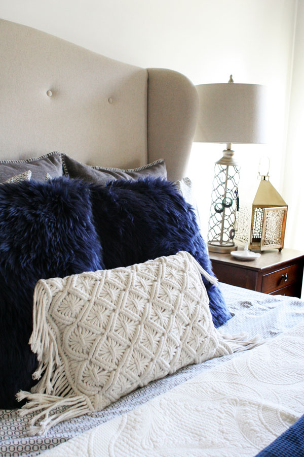 Eclectic Christmas Bedroom with Upholstered Headboard, White Quilt, Sheepskin Pillows, Crocheted Pillow, and Pom Pom Throw