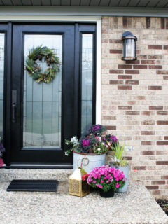 Black Front Door with Christmas Wreath and Pink Flowers in Planters.
