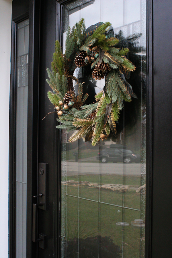 A black front door decorated for Christmas with a simple magnolia, evergreen, and pinecone, wreath