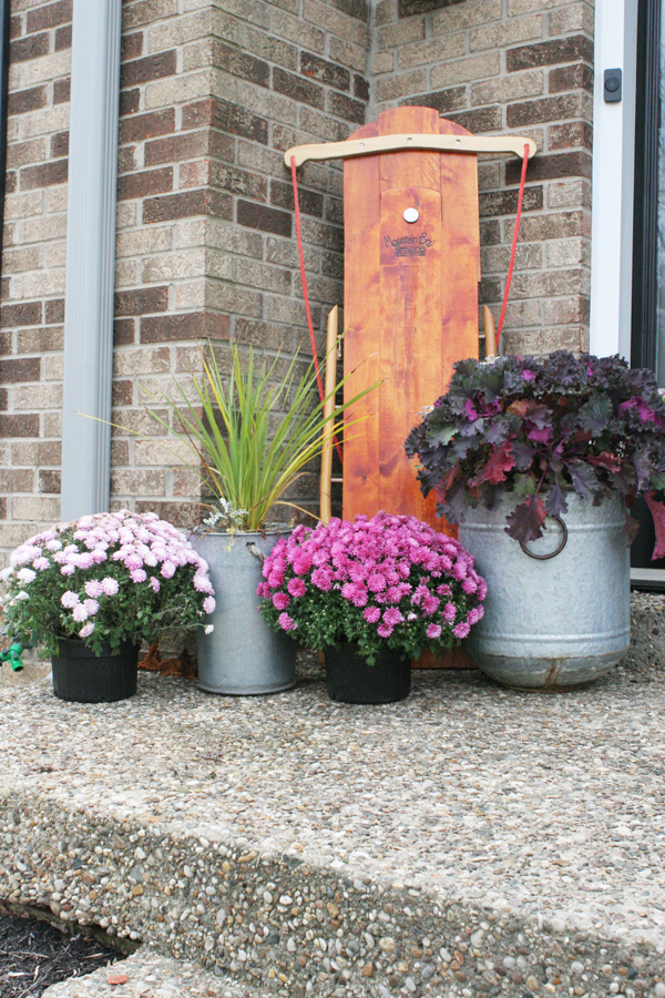 Christmas Porch Decorations include a Wood Sled and Pink Flowers in Planters