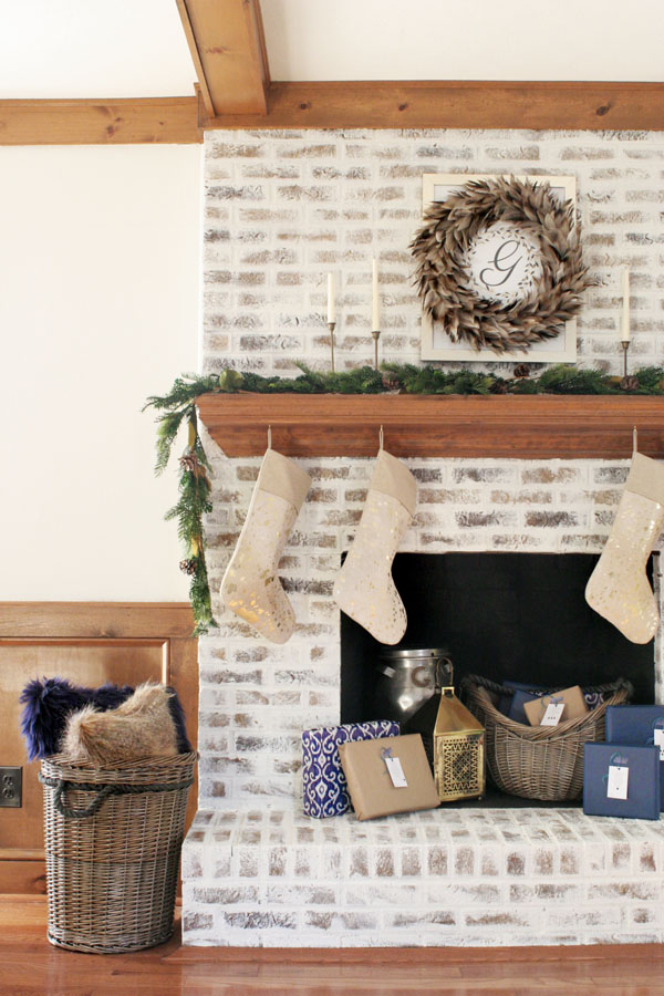 German Schmear Brick Fireplace with Christmas Decorations - Feather Wreath, Brass Candles, and Garland. Christmas Mantel Ideas on a German Schmear Brick Fireplace.