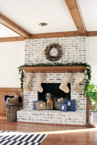 Christmas Fireplace Decorations and Christmas Mantel Ideas including gold stockings, blue Christmas decor, and a white brick fireplace.