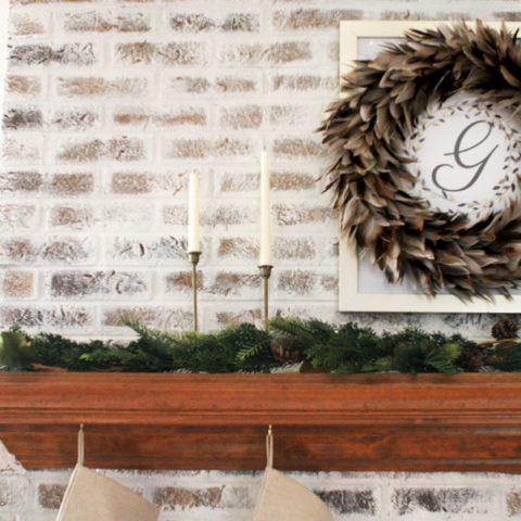 Fireplace Christmas Decorations with Feather Wreath, Brass Candles, and Garland. Christmas Mantel Ideas on a German Schmear Brick Fireplace.