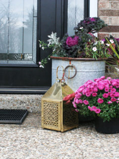 Christmas front porch decor with a brass lantern and pink flowers