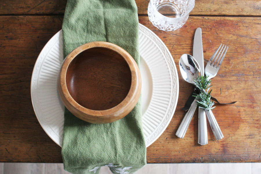 Rustic Christmas Table Place Setting with green napkins, white plates, and a christmas napkin ring