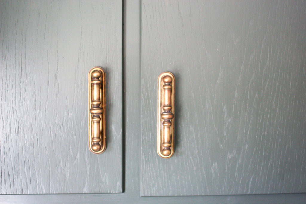 green cabinets with brass pulls