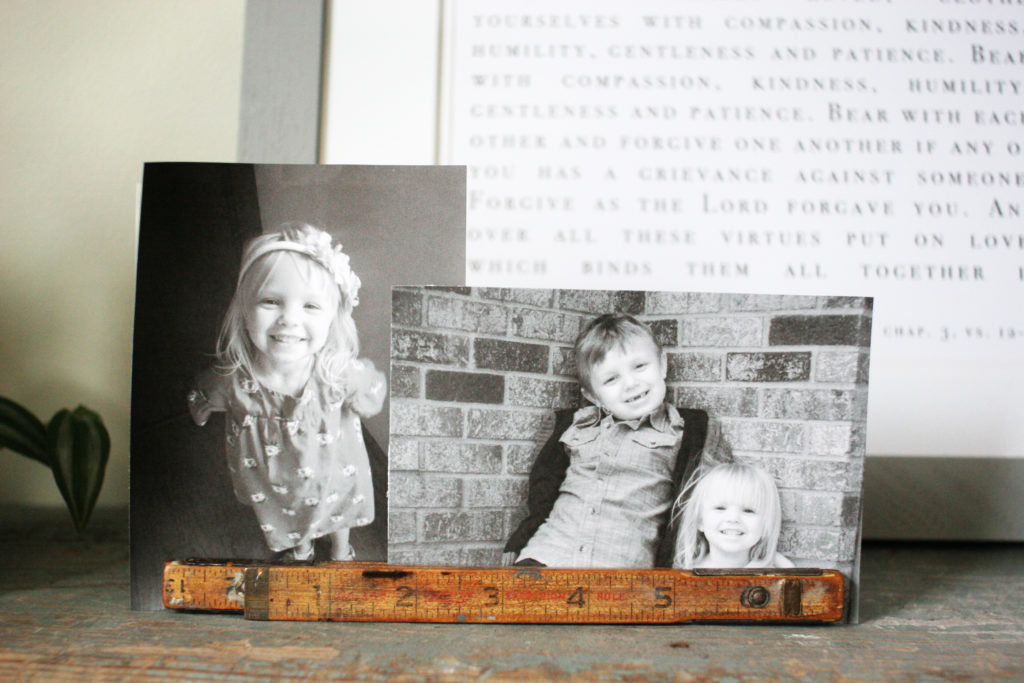 family photos in vintage folding ruler on laundry room shelf