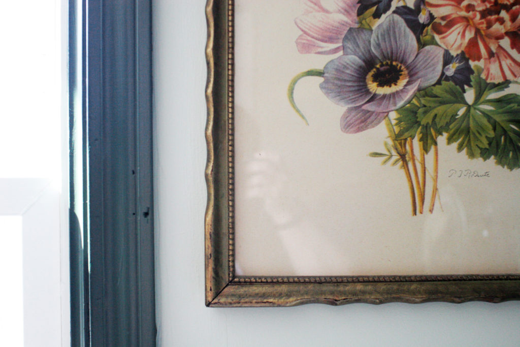 green trim and vintage artwork in vintage laundry room