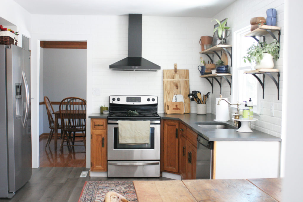 kitchen with white walls, brick backsplash, and dark gray countertops