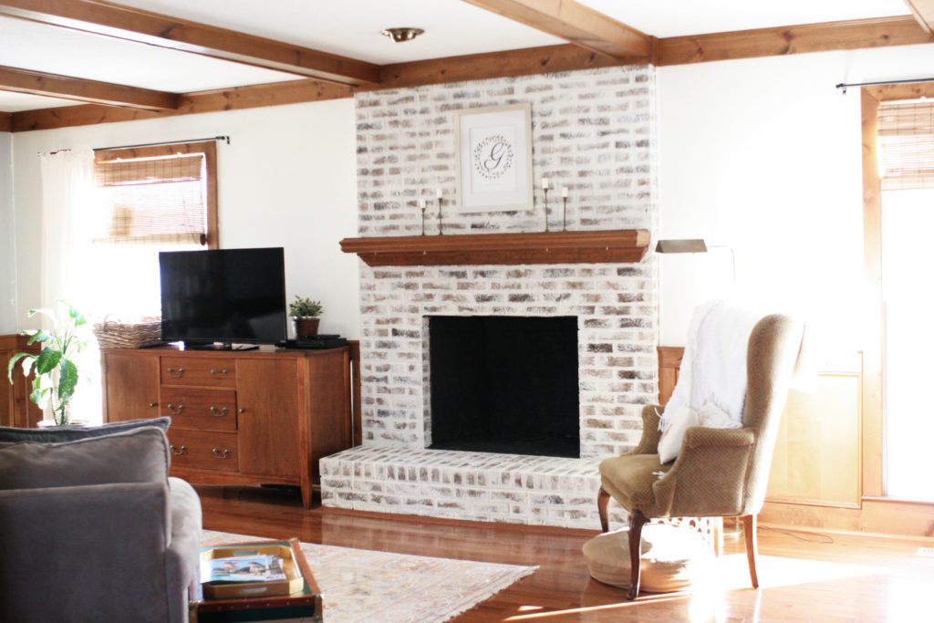 german schmear brick fireplace in living room with wood trim