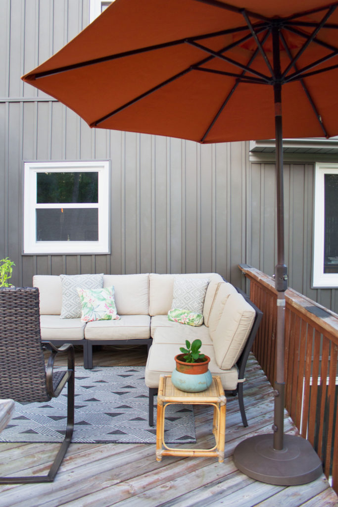 modern cottage with gray board and batten vinyl siding, outdoor couch on deck