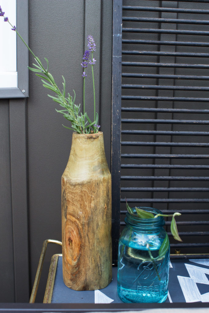 lavender in a wood vase, mason jar with clipping, and dark vinyl siding